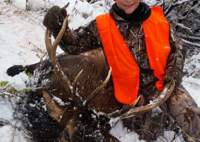 Small hunter in the snow with his Elk