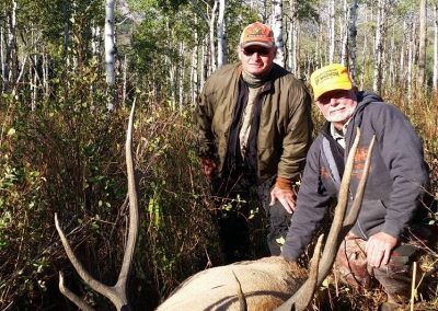 Hunters with their Elk in grove of trees at Wolf Mountain Ranch
