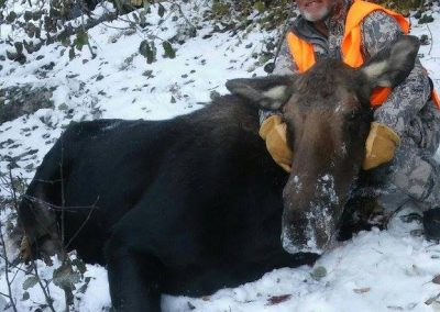 Hunter with his moose in the snow