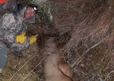 Hunter with his kill in a meadow at Wolf Mountain Ranch