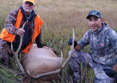 Guide and Hunter with their Elk in Meadow