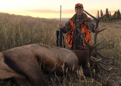 Hunter with his Elk in meadow at Wolf mountain Ranch